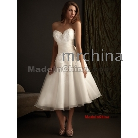 A sweet tea-length gown featuring three-dimensional detailing throughout. The fitted bodice has a sweetheart neckline and ruched sash defining the waist organza wedding dresses